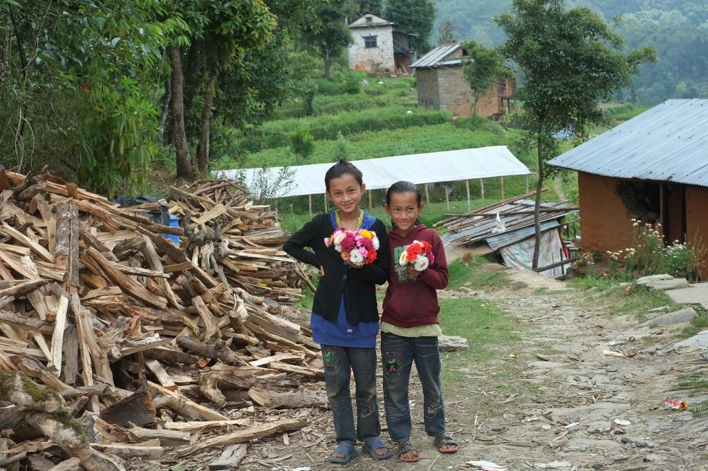 Two girls holding flowers to welcome relief workers. A temporary housing on the background.