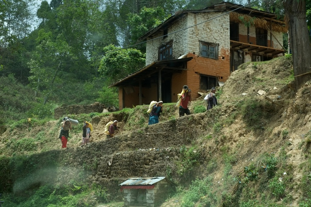 People carrying relief materials to their homes.  Buddhist shrine at the side of the road.