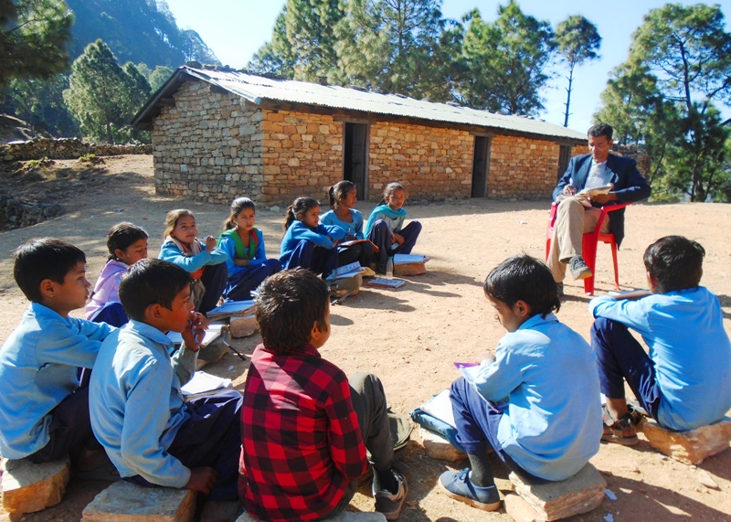 Cold weather and inadequate indoor lighting urges the teacher, Mr. Krishna Bahadur Chand, to take his grade 2 students outside. Sitting on stones, class is resumed under the warmth of the winter sun.