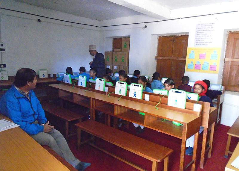 OLE Nepal's Senior Training Manager, Tika Raj Karki, observing laptop integrated class at Nanigad Primary School in Nagarjun. Trainers from OLE Nepal visited each program school to observe and provide feedback regarding their integration of digital content.