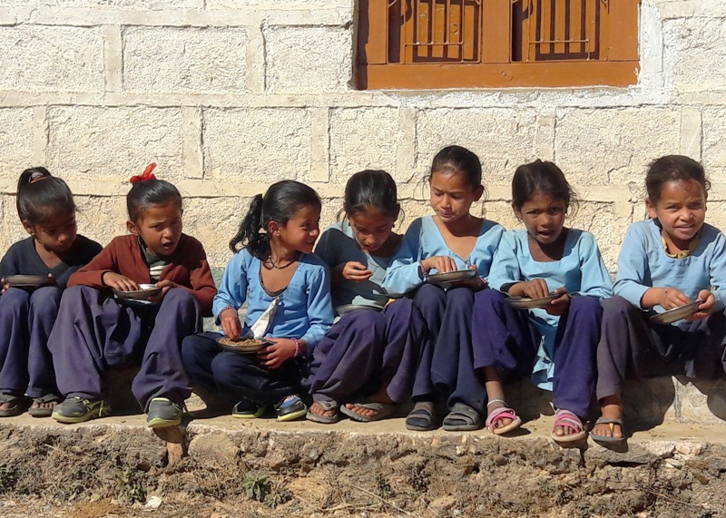 "Students enjoying their plate of nutritious 'suji'. UN World Food Programme provides school meals to remote schools across the far-west region of Nepal under their ""Food For Education"" program."