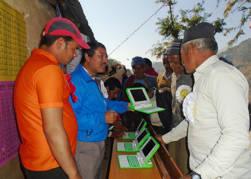 OLE Nepal's Senior Training Manager, Tika Raj Karki, explaining about the laptop program with members of the Balara community at the school's education fair.